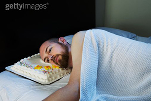 A man with a beard lays in bed using a sheet cake as a pillow.
